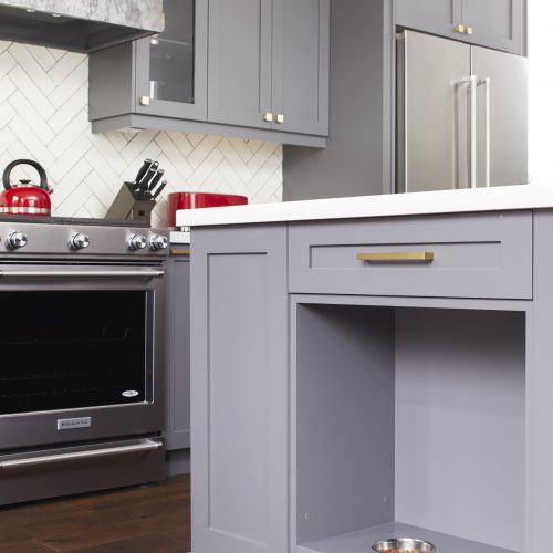 toronto small space home - kitchen island with built in custom pet feeding centre - how to build in pet food area - dark gray cabinetry - linda mazur design
