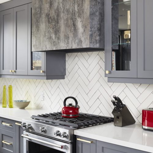 toronto home renovation in the annex - small space open concept living - custom kitchen range hood distressed paint finish with glass cabinets and dark grey kitchen cabinetry white quartz counters - gold lighting and scandi barstools - white chevron tile backsplash - linda mazur design toronto designer