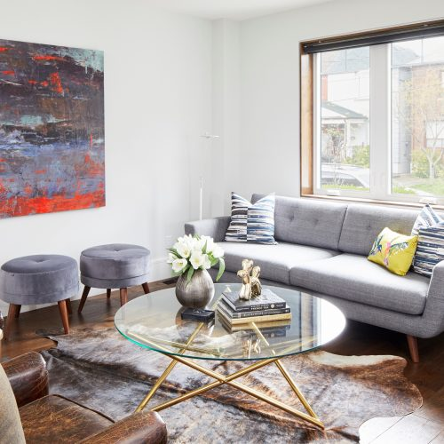 """annex home - featured in Toronto Homes Movado Homes """"the Jewel in the Town"""" - modern open concept home - modern living space with scandi sofa and cow hide rug, leather distressed club chairs and glass coffee table, black windows with wood jambs - bright art work - linda mazur design toronto design full service design build renovate"""