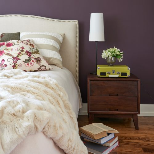 bedroom image with upholstered headboard and faux fur throw - deep purple aubergine wall colour - cream neutral bed linens pattern play - linda mazur design