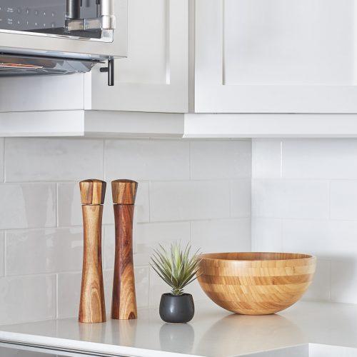 two tone toronto condo kitchen - york region condo renovation - warm wood accessories for your kitchen - white quartz counter tops - black kitchen hardware - microwave over range - linda mazur design