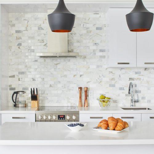 corktown toronto condo kitchen renovation - all white kitchen with marble backsplash white quartz waterfall counter - black pendant lights - linda mazur design toronto designer