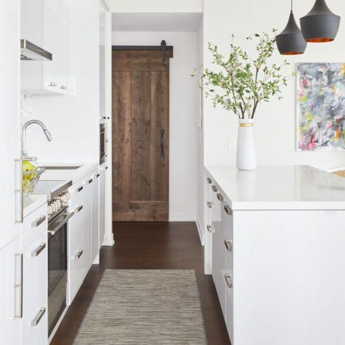corktown condo renovation - wood floors - barn door custom millwork - white kitchen with waterfall white quartz counter - bright artwork - linda mazur design full service canadian designer