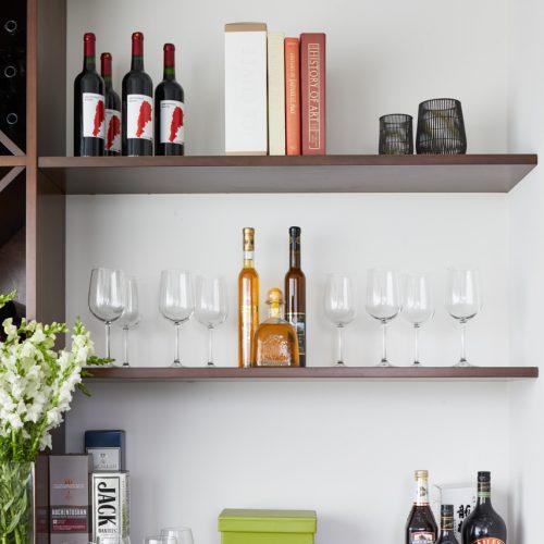 corktown small condo - custom millwork built in bar area - open shelving bar display - linda mazur design small space living