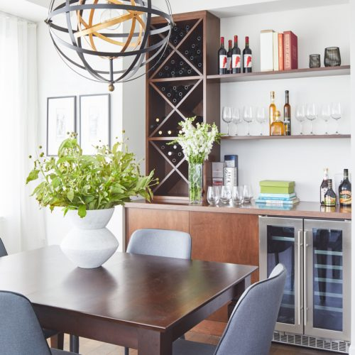 toronto condo in corktown - custom millwork bar area with bar fridge - dining room wood table with blue upholstered dining chairs - dining room chandelier - small space storage - toronto designer linda mazur design