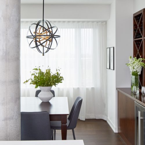 corktown condo living - open concept living dining room space with custom sheer window treatments and custom millwork bar area, wood table with upholstered blue dining chairs - linda mazur design toronto designer