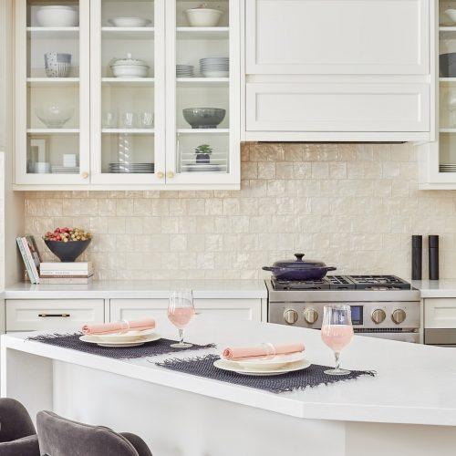 markham luxury family kitchen renovation - cream white custom millwork cabinets and range hood with glass cabinets - white quartz waterfall countertops black porcelain flooring - linda mazur design canadian designer
