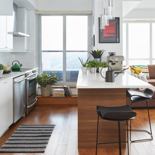 toronto condo renovation - scandi kitchen white and wood cabinetry with white quartz counter tops - wood floors and white subway tile backsplash - small space living - open concept living - toronto designer Linda mazur design - walnut kitchen peninsula - toronto condo living - black modern counter stools - using plants for decorating