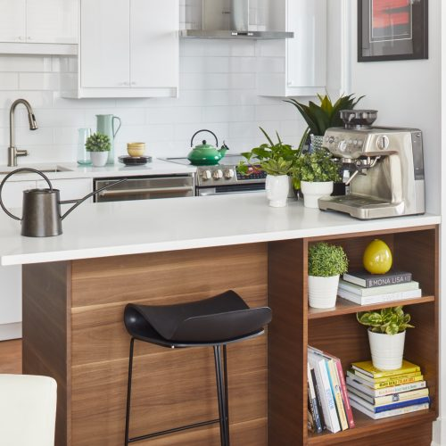 toronto condo renovation - scandi kitchen white and wood cabinetry with white quartz counter tops - wood floors and white subway tile backsplash - small space living - open concept living - toronto designer Linda mazur design - walnut kitchen peninsula - toronto condo living - black modern counter stools - using plants for decorating - custom millwork walnut peninsula with added storage for small space open concept living