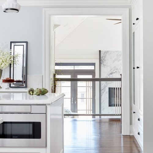 historic toronto homes - luxury family home renovations - white and black kitchen - custom kitchen millwork - quartz countertops - wood flooring - glass railing - kitchen overlooking sunken sunroom - marble fireplace - vaulted ceiling - linda mazur design toronto designer
