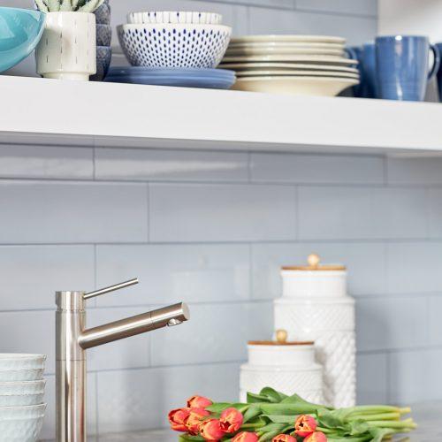 white luxury kitchen - modern luxury kitchen, family home - kitchen with open shelving -quartzite countertops - subway tile backsplash- bar sink - blue kitchen dishes and accessories on open shelf - linda mazur design - toronto designer