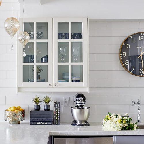 toronto condo kitchen renovation - white glass custom cabinetry with quartz countertop - white subway tile backsplash and pretty glass pendants - linda mazur design
