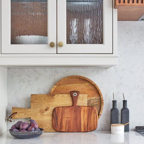mississauga custom kitchen renovation - wood custom range hood with fluted detail - transitional - glass cabinet door fronts - quartz counter and backsplash - linda mazur design toronto designer